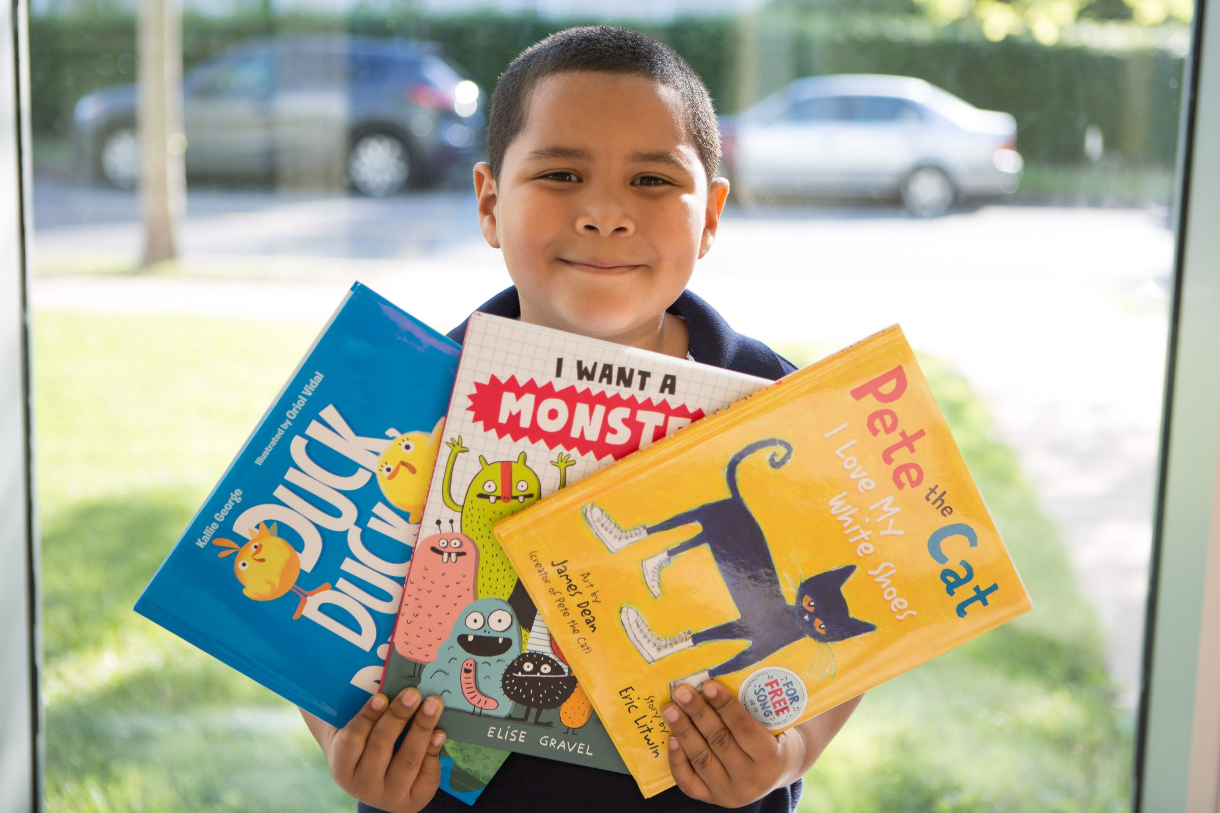 NHR student happily displays books he received in a giveaway.