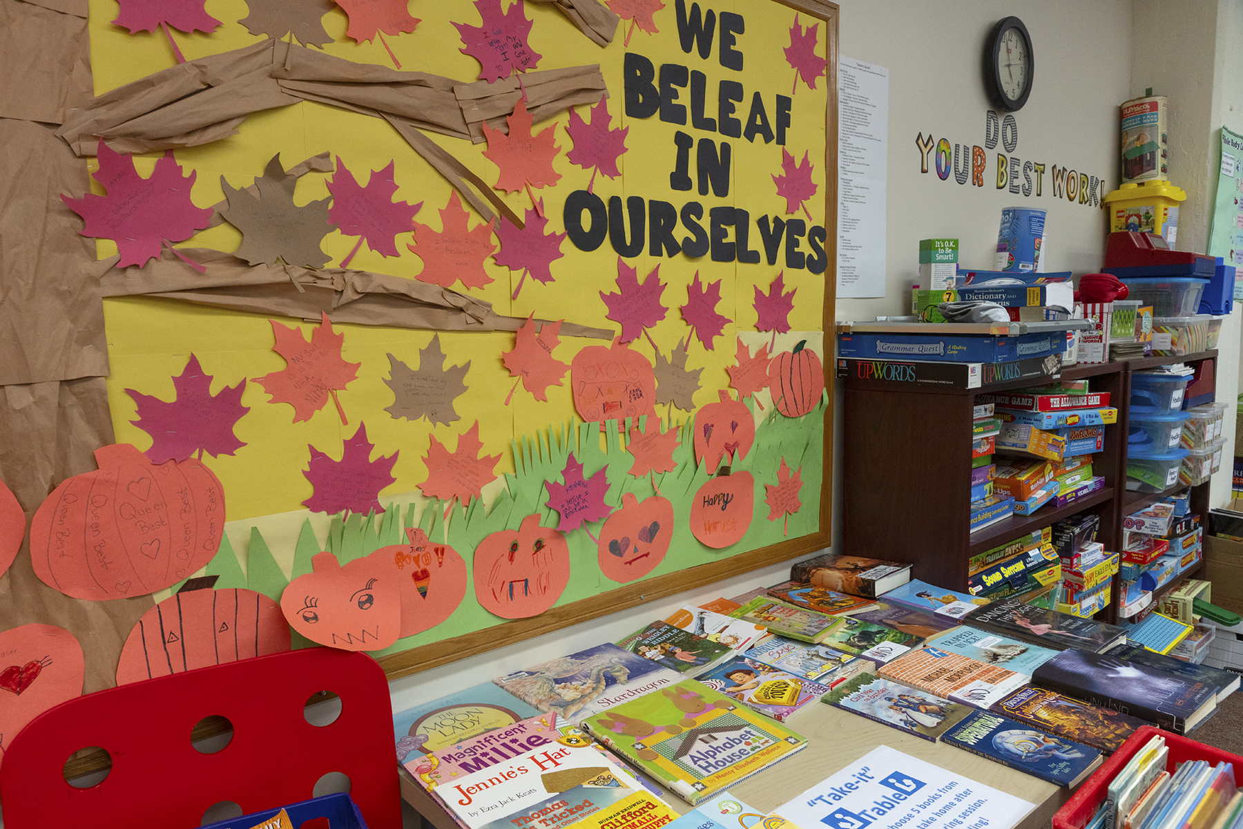 A fall-themed bulletin board at a NHR location and a table full of books for a student giveaway