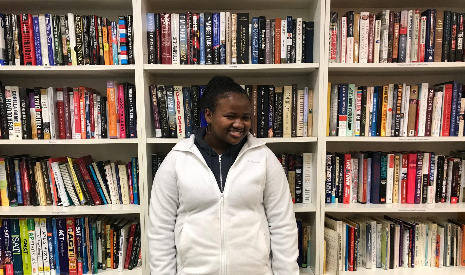 Della Smith, NHR student, stands in front of shelves in the Book Bank.