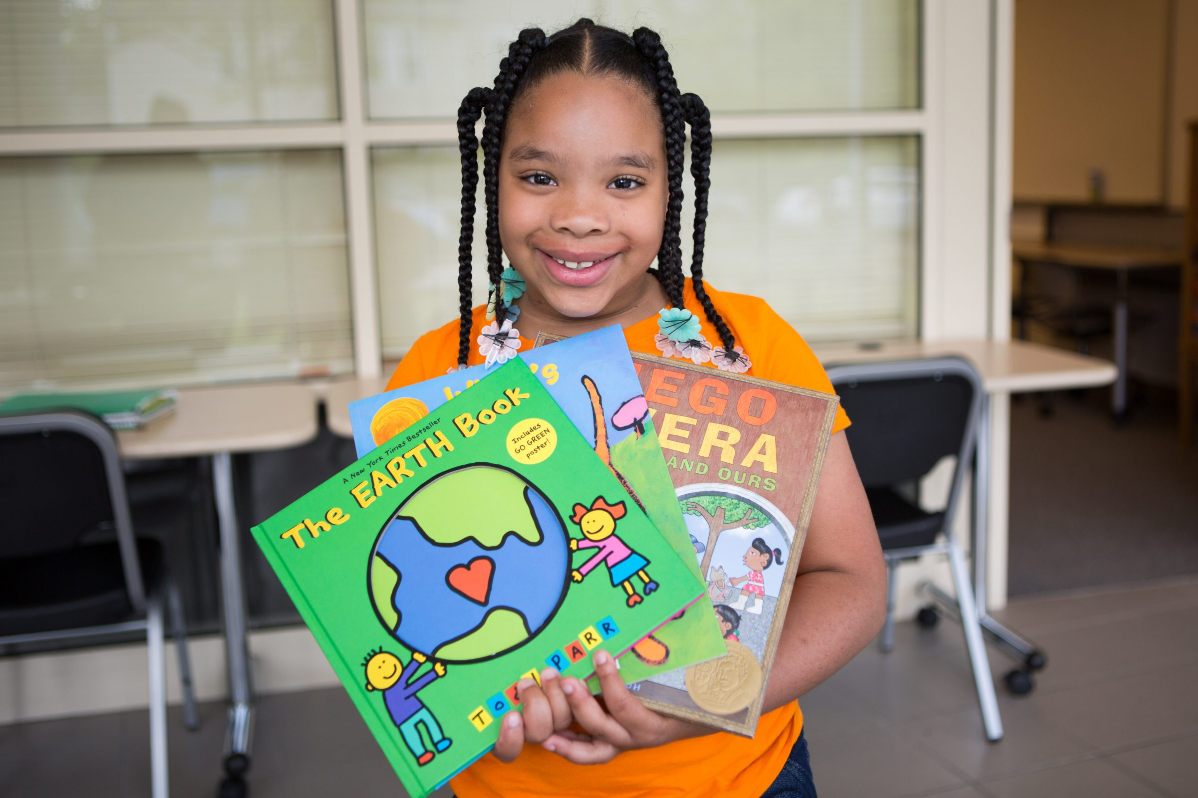 NHR student happily displays books she received in a giveaway.