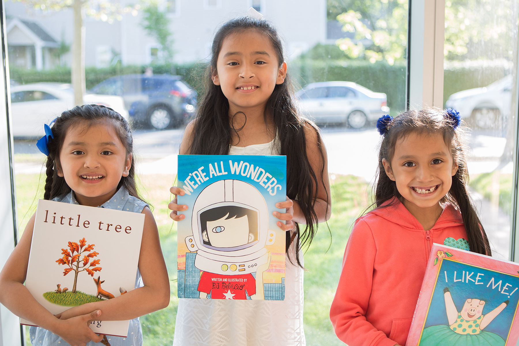 NHR students happily display books they received in a giveaway.