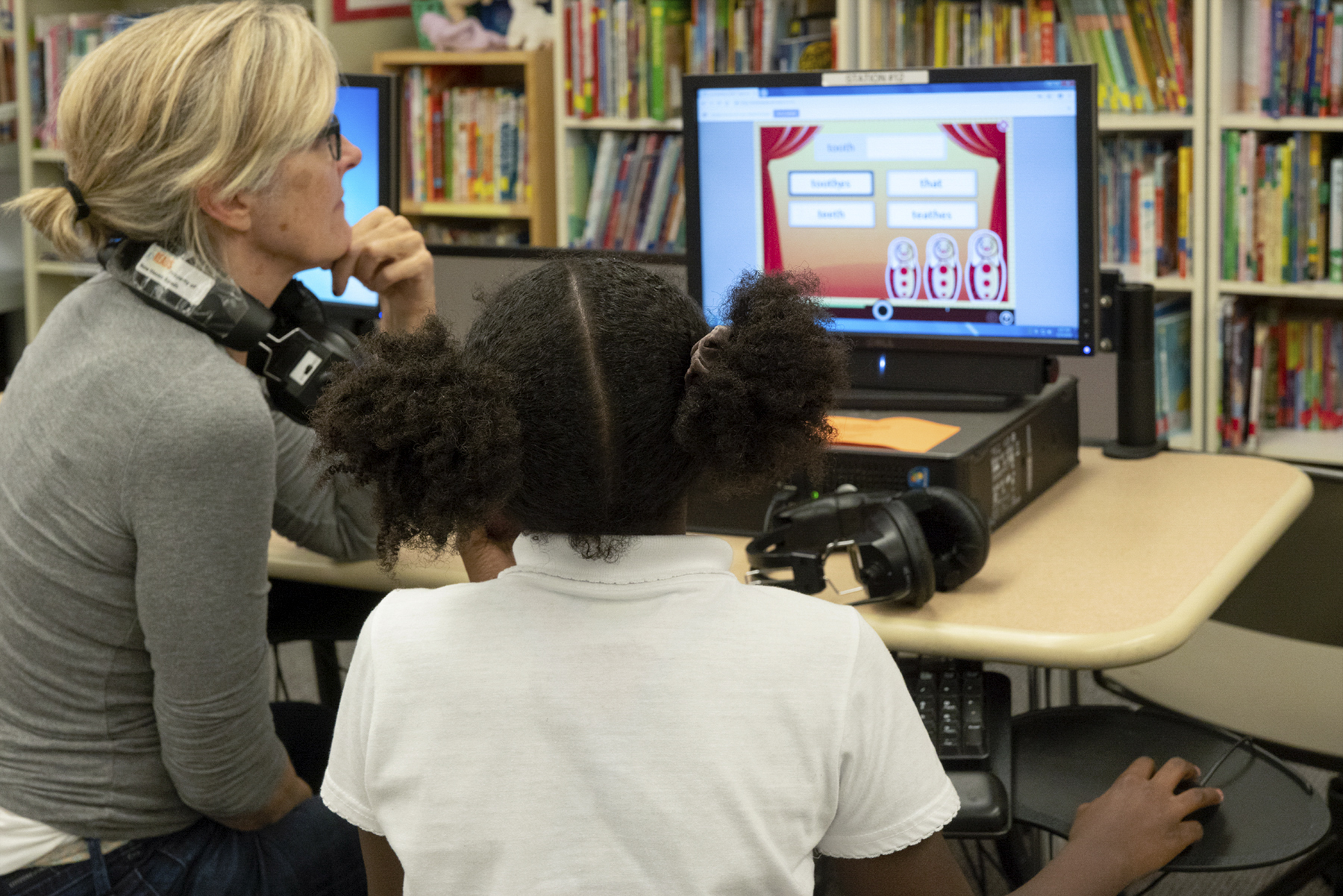 NHR student works on a computer-based literacy program as her tutor looks on.