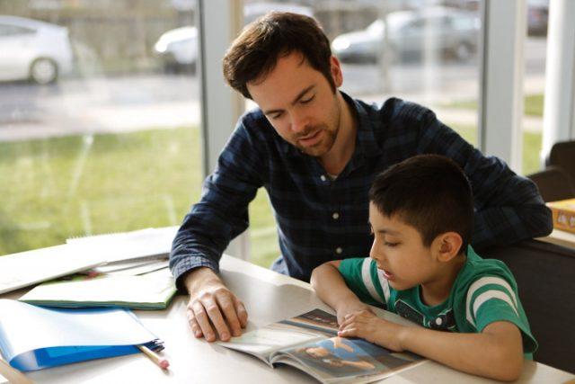 NHR tutor helps a student read aloud.