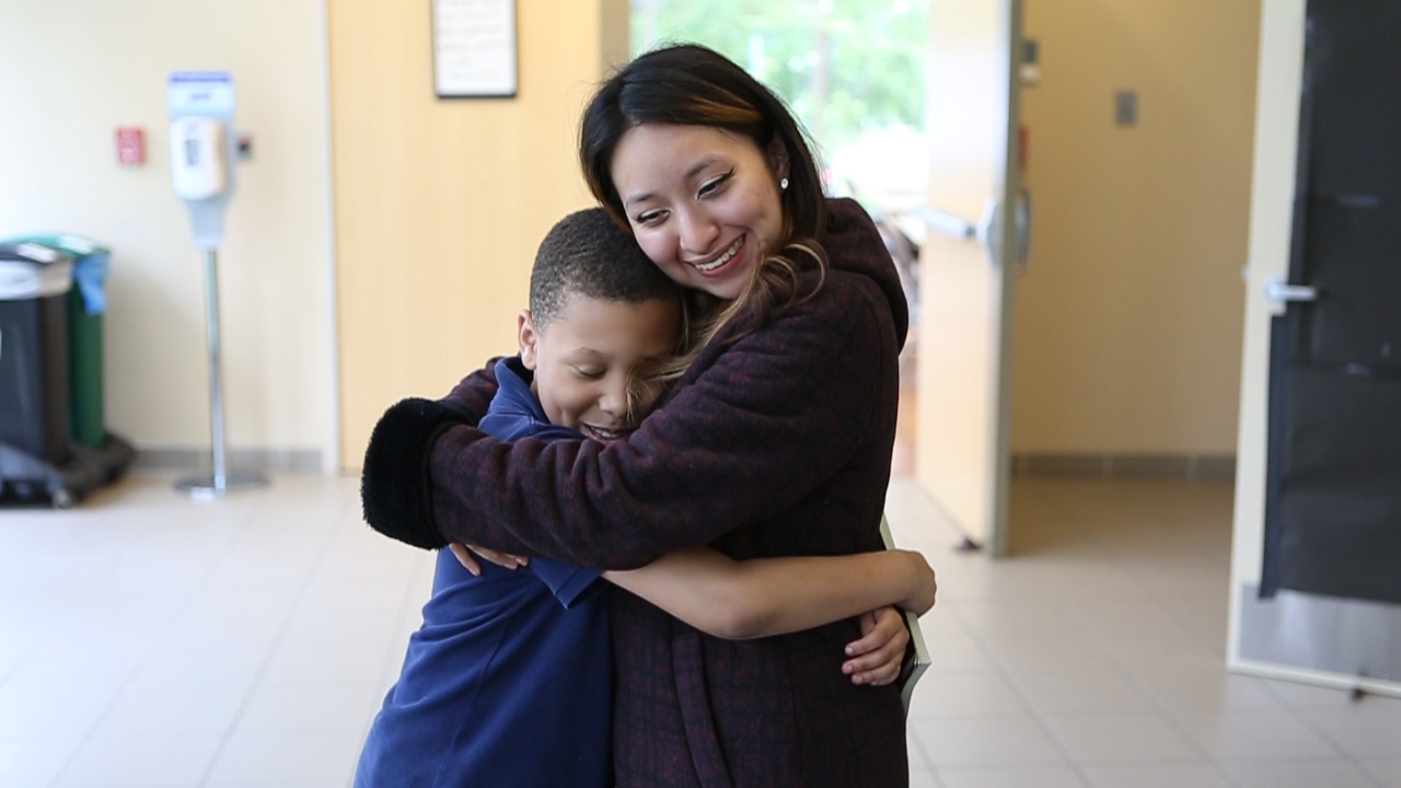 NHR student and tutor smile as they hug each other.