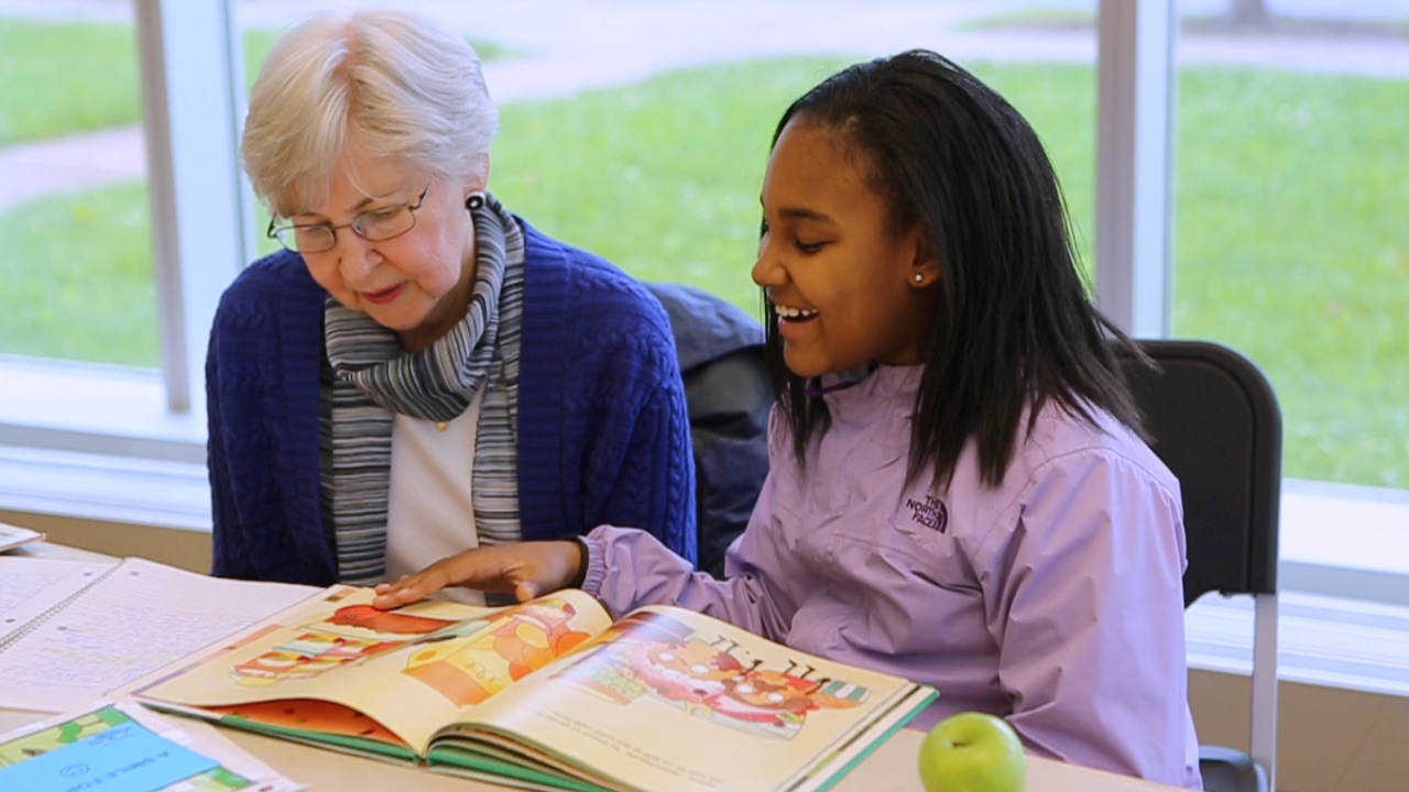 NHR student reads aloud with their tutor.
