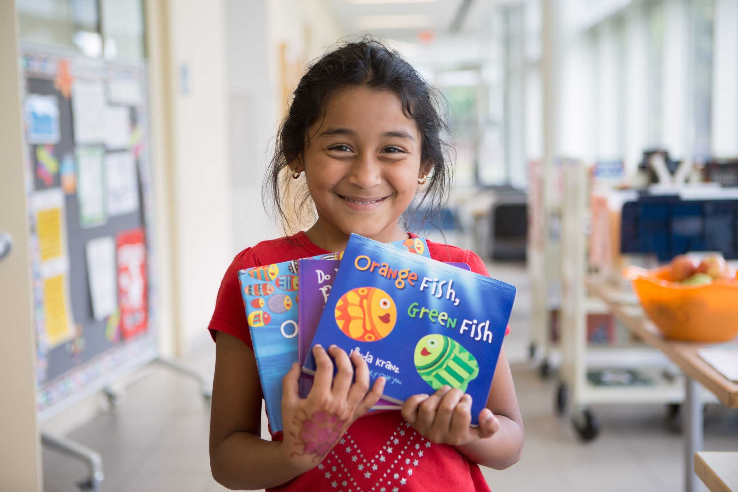 Smiling NHR student displays books she received in a giveaway.