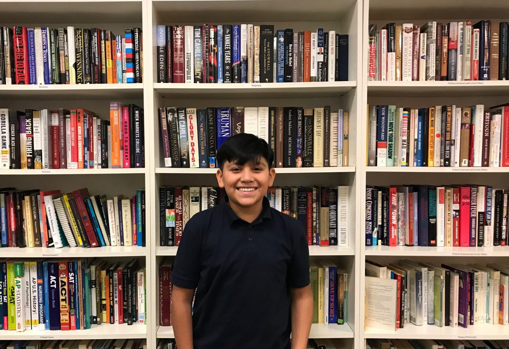 Jonathan Cuapio, NHR student, stands in front of shelves in the Book Bank.