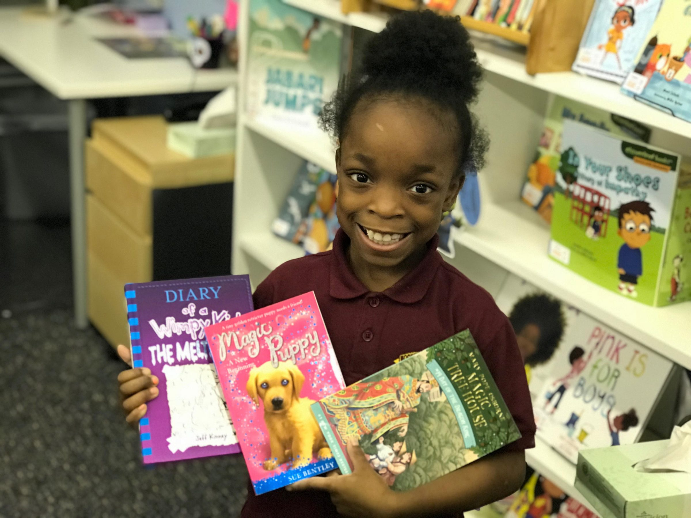 NHR student happily displays her book selection.