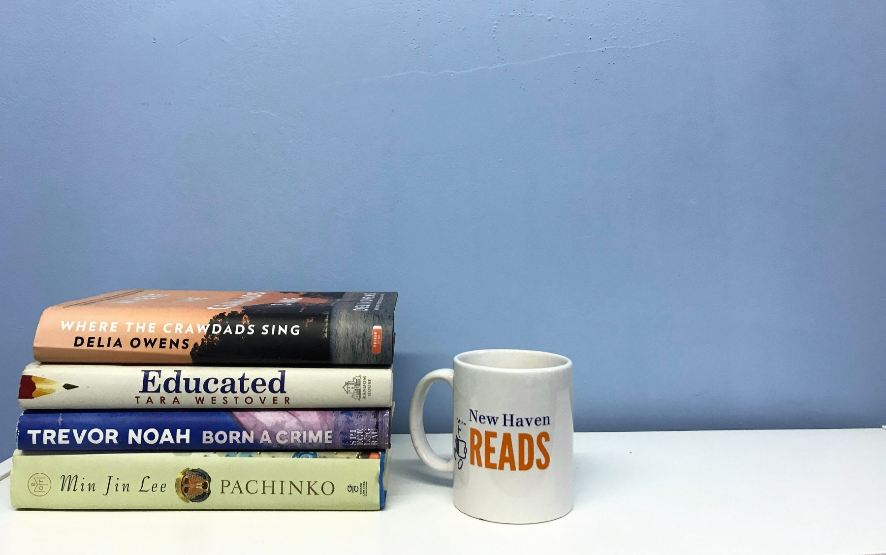 A stack of books sits on a table by an NHR mug.