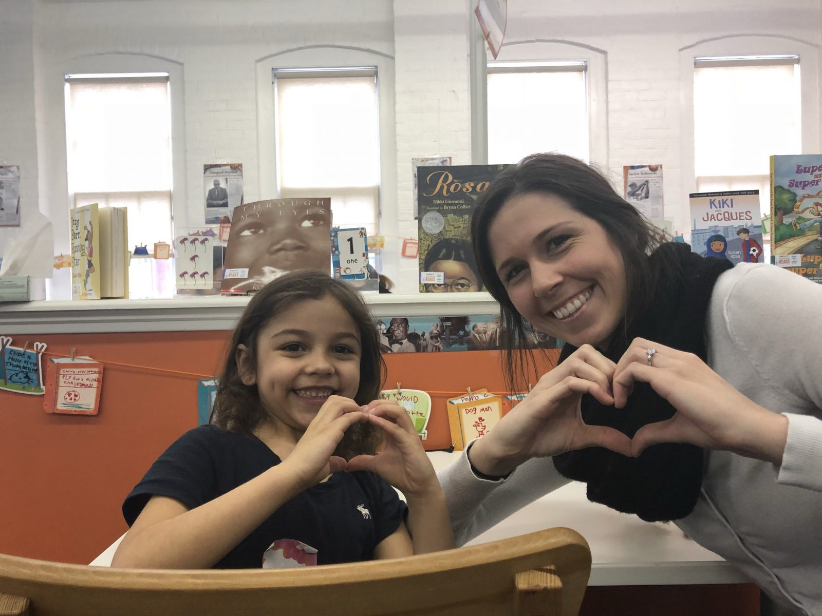 NHR student and tutor make heart signs with their hands.