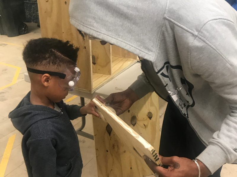 two volunteers working with wood