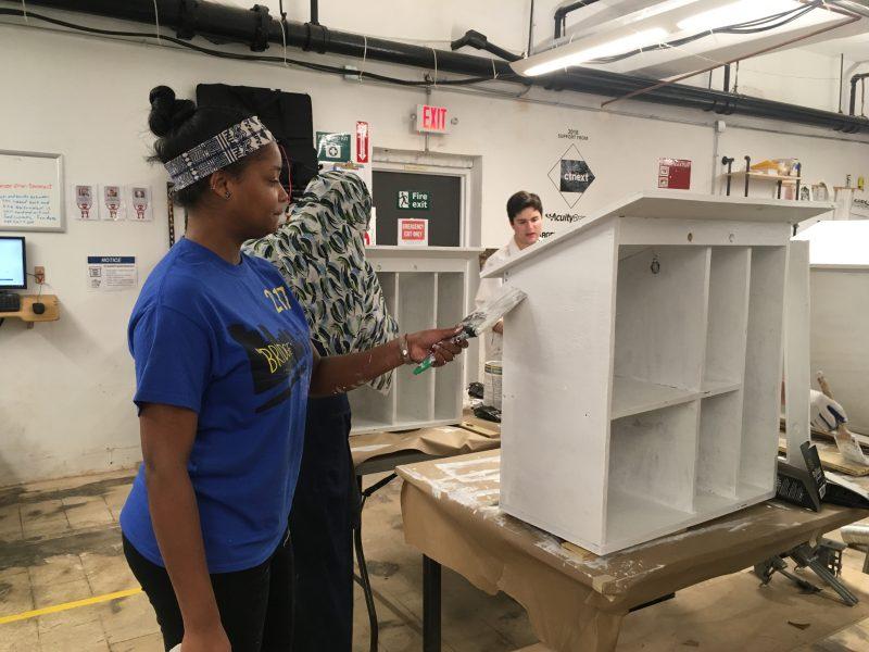volunteer applies primer to a book box