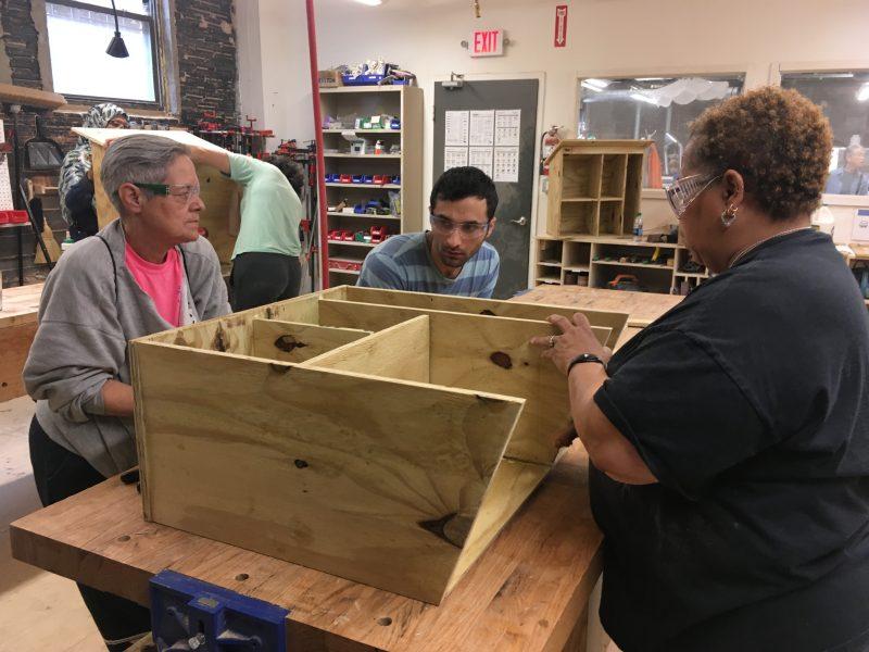 three volunteers construct a book box