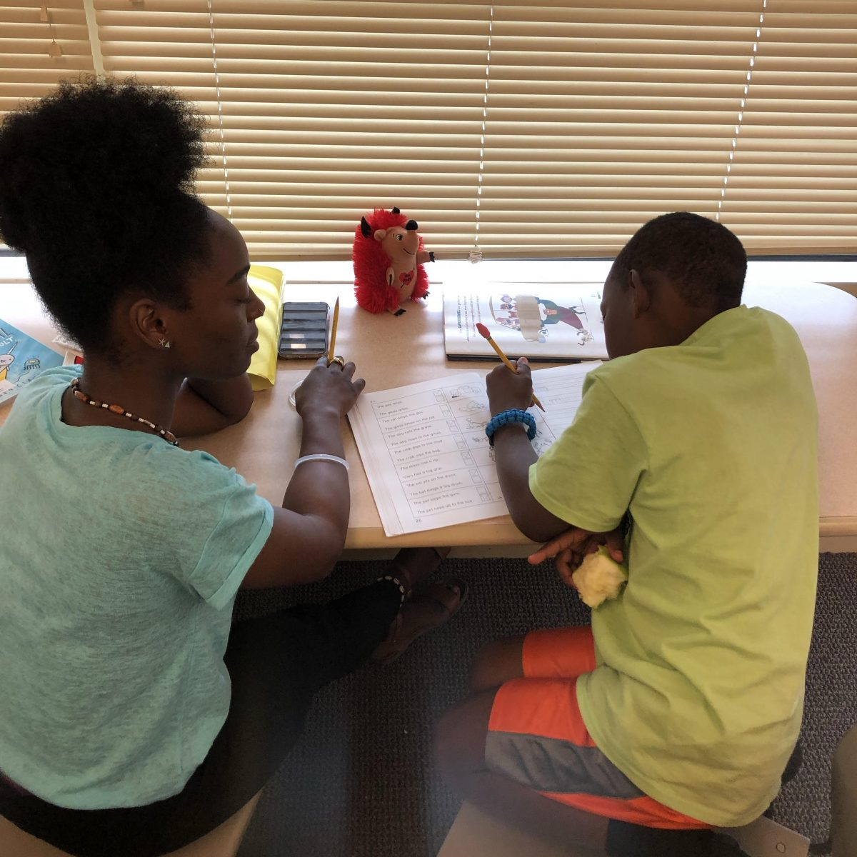 Deja works with a student during a tutoring session.