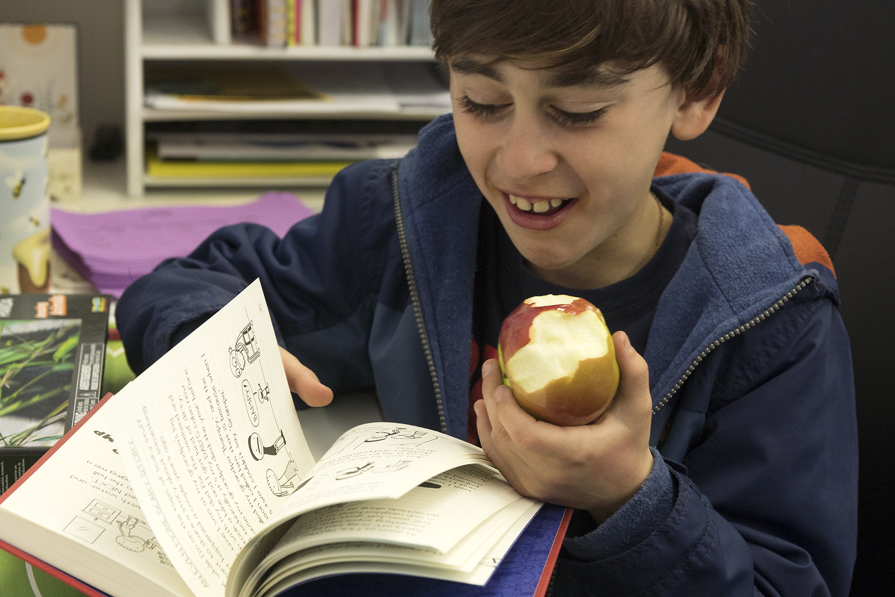 Student reading a chapter book and eating an apple