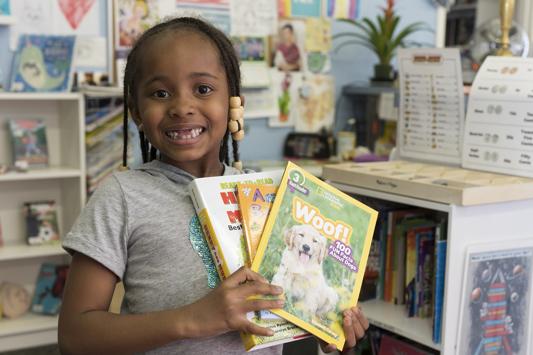 A student smiles with three books