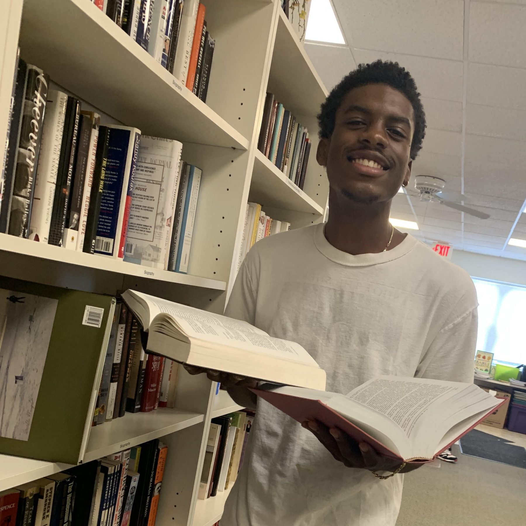 A student smiles holding two books.